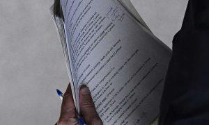 O documento fotografado sendo carregada por um oficial britânico não identificado prestes a entrar numa reunião sobre a crise na Ucrânia, revela a intenção de Londres em não ameaçar o capital russo no país (Steve Back)