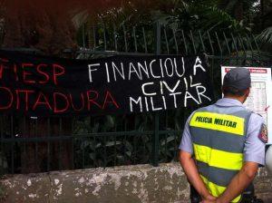 Policiais observam as faixas dos manifestantes (Foto: Igor Carvalho)