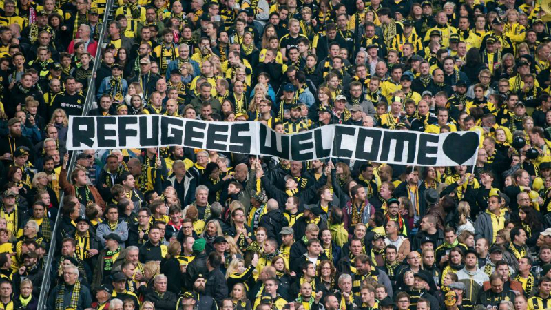 """Faixa levantada pela torcida do Borussia Dortmund diz: """"Refugiados, sejam bem-vindos"""" (Reprodução/Twitter)"""
