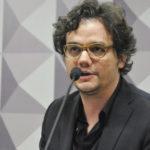 Wagner Moura falando ao microfone de óculos de grau. Tem a barba rala e os cabelos mais compridos, ondulados. Usa terno e camisa preta.