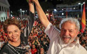 Lula e Dilma Rousseff sorrindo e dando as mãos na frente de uma multidão