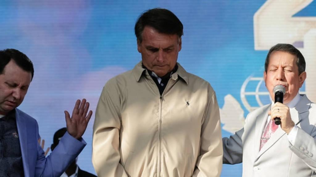 A imagem mostra o Presidente Jair Messias Bolsonaro entre Davi Soares e R.R. Soares, pastor e missionário da Igreja Internacional da Graça de Deus. Os três estão de olhos fechado e orando.