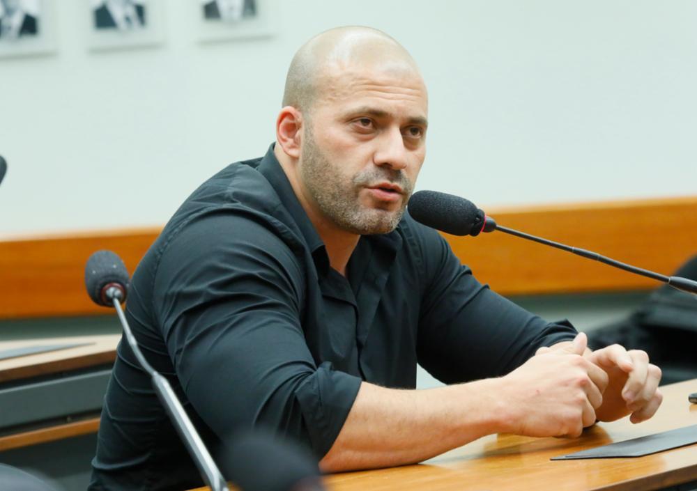 Daniel Silveira sentado em uma mesa de madeira e falando ao microfone. É careca, forte e usa camisa de manga comprida preta e justa