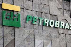 Logo da BR Petrobas em verde e amarelo na frente de uma parede de pedras cinza
