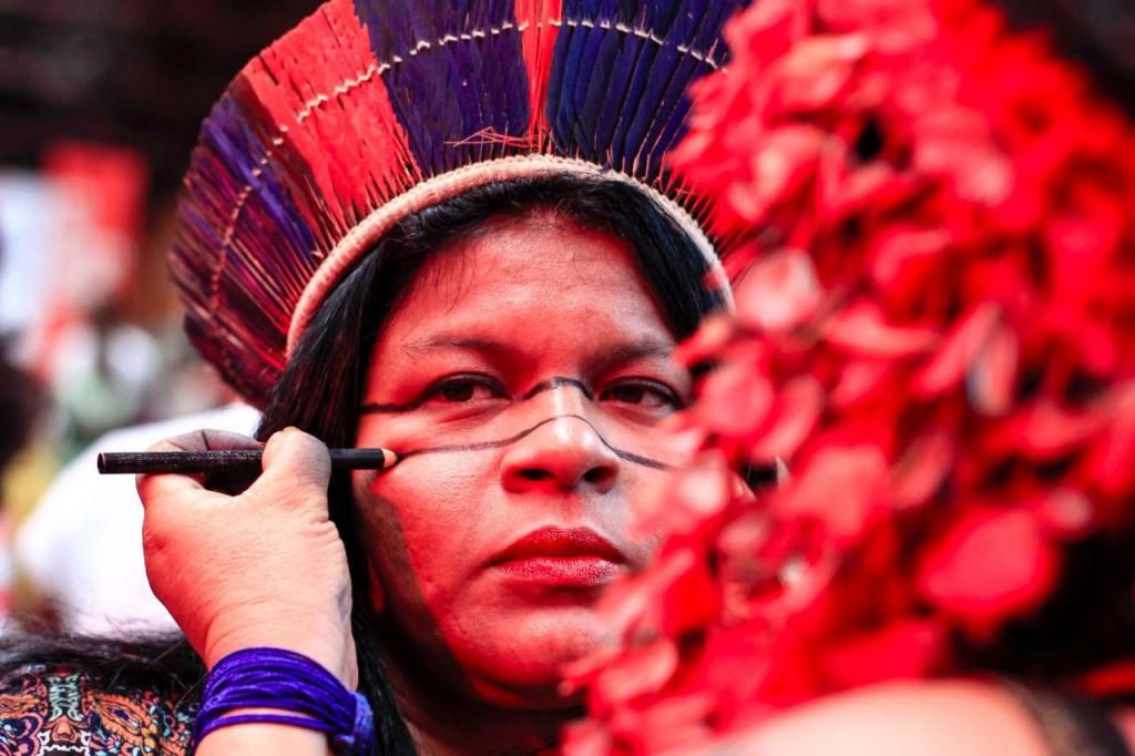 Pessoa pintando o rosto de indígena com um lápis preto. Pessoa que está sendo pintada tem o rosto sério, uma um cocar azul-marinho e vermelho e está com um risco horizontal abaixo dos olhos. A outra pessoa está de costas e só dá para ver o braço