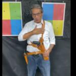 Roberto Jefferson segurando uma arma. Usa calça jeans e camisa branca e tem a mão pousada no peito. Está em pé posando para a foto
