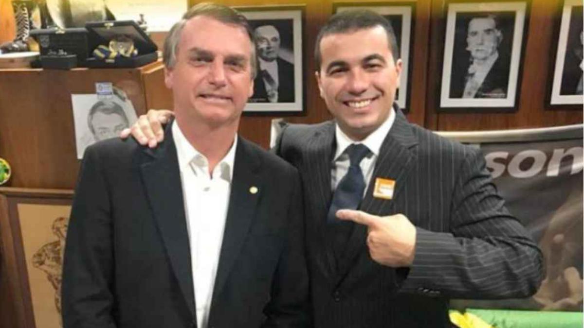 dois homens lado a lado, um apontando o dedo para o outro. À esquerda, Jair Bolsonaro e à direita, Luis Miranda. Ambos estão de terno