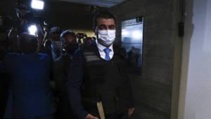 Homem de máscara, terno e gravata chegando a um espaço com colete a prova de balas. A foto é escura, mas dá para ver pessoas atrás dele