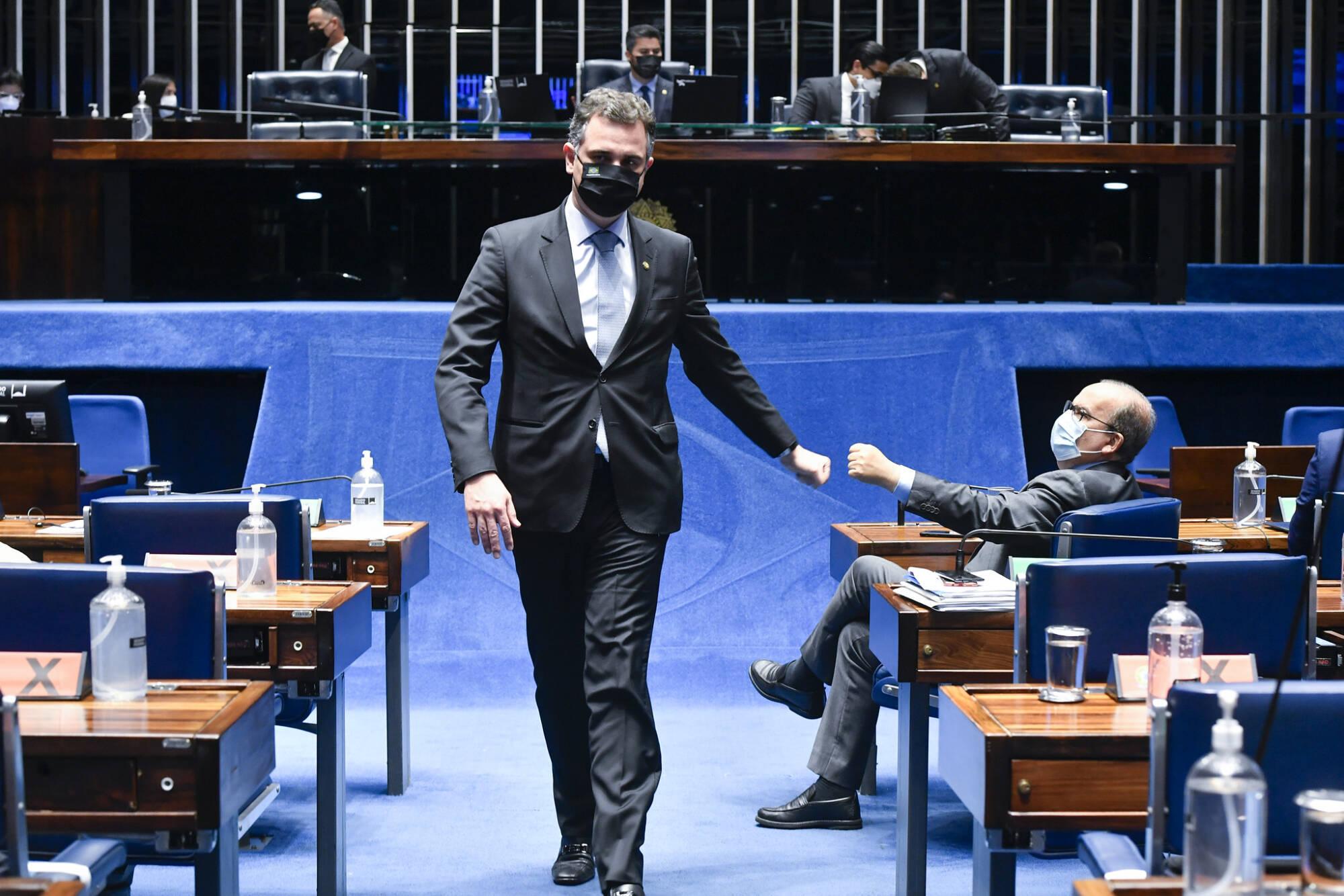 Rodrigo Pacheco andando no Senado de terno preto, camisa e máscara e com a mão dando um soquinho na mão de outro homem senado em uma cadeira