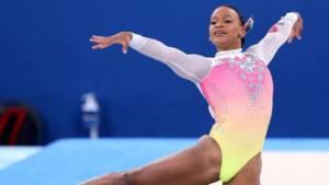 Ginasta Rebeca Andrade fazendo pose com uma perna esticada e os braços esticados, um para cada lado. Ela tem uma feição feliz e usa um collant colorido, com rosa, verde, amarelo e transparência