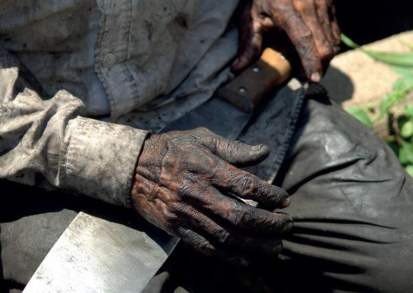 Homem com as mãos sujas segurando uma faca grande