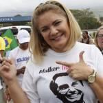 """Mulher loira de tiara posando para a foto fazendo """"arminha"""" com a mão e com uma camiseta com o rosto de Bolsonaro. Ela sorri."""