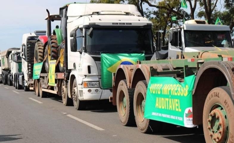 Vários caminhões parados um atrás do outro com bandeiras do Brasil