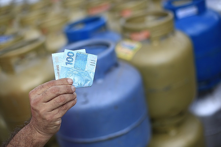 Botijões de gás azuis e dourados desfocados e, na frente, com foco, uma mão segurando uma nota de R$ 100