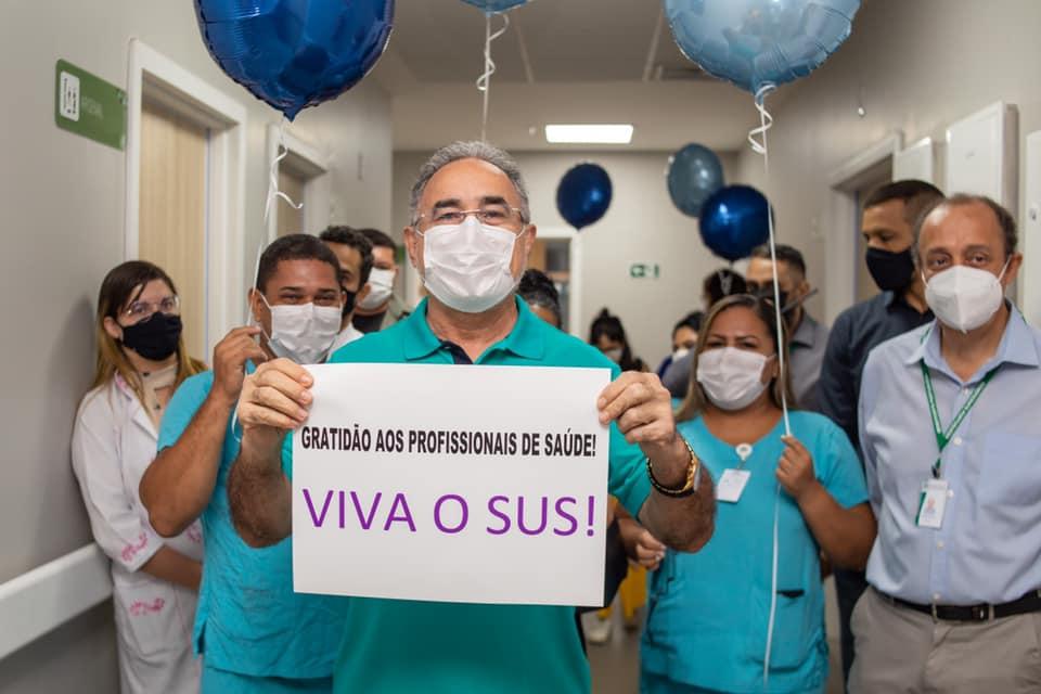 """Homem de camiseta azul com placa escrita """"Viva o SUS"""". Profissionais de saúde segurando balões azuis atrás dele, no corredor de um hospital"""