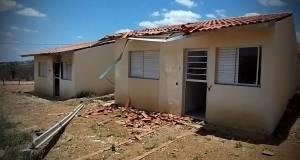 Duas casas simples, uma ao lado da outra, semidestruídas. Uma delas tem telhas caídas à frente e o telhado depredado