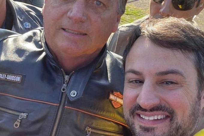 Bolsonaro com jaqueta de couro sorrindo para uma selfie ao lado de um homem branco, de barba curta e cabelo castanho dividido ao meio, também sorrindo