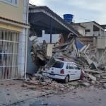 Escombros de uma casa desabada sobre um carro branco