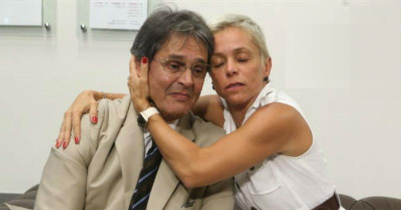 Filha de Roberto Jefferson, mulher loira de cabelos curtos, consolando ele abraçada e com a mão sobre o seu rosto. Ele está com uma cara triste. Usa óculos de grau, tem cabelos grisalhos e veste terno bege com gravata azul.