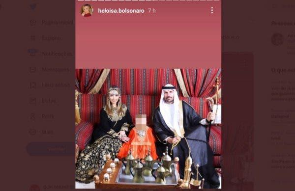 Mulher e homem com trajes típicos árabes, com um bebê no meio, também em trajes típicos. Eles estão sentados lado a lado em um sofá com uma mesa cheia de prataria. Ela usa um vestido estampado e acessório na cabeça, enquanto ele usa uma roupa de sheik, com um lenço que cobre a cabeça